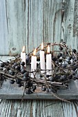 Four lit candles in wreath of sloe branches
