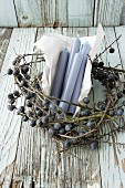 Blue candles and paper in wreath of sloe branches
