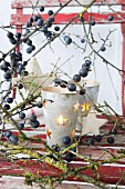 Candle lantern with punched stars amongst sloe branches on red chair