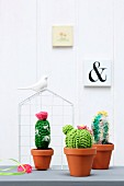 Crocheted cacti in terracotta pots in front of ornamental wire house