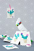 Cards printed with cactus motifs arranged on cockatoo figurine