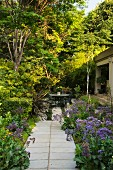 Path leading through summery garden to seating area outside house