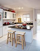 Moderne Küche mit Kochinsel, zwei Barhocker aus Holz am Thresen