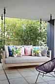 Swing couch with colourful scatter cushions on roofed terrace