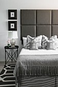 Bed with upholstered headboard in elegant bedroom in shades of grey
