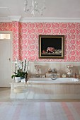 Pink floral wallpaper above bathtub in bathroom