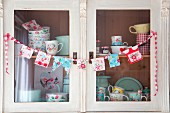 Hand-sewn bunting and floral crockery on shelves of kitchen dresser