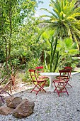 White table with red chairs on gravel in front of exotic plants