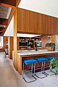 Custom-made room divider with integrated kitchen counter and hatch, bar stool with blue cover