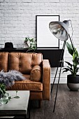 Leather sofa in the masculine living room with brick wall