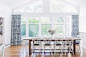 Langer Esstisch mit Stühlen im ländlichen Stil vor Fensterfront