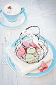 Macarons in hand-made wire basket and cup of cappuccino