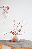 Branches of crab apples in vase and pear on wooden table in front of candy cane hung from coat rack