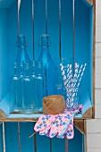 Aufbewahrungregal aus blau gestrichenen Holzkisten mit Flaschen, Garnrolle, Strohhalmen und Gartenhandschuhen