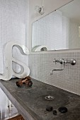 Concrete washstand, vintage-style wall-mounted taps and mirror in bathroom with white mosaic wall tiles
