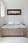 Doppelbett und moderne Kunst in Schlafzimmer mit weißem Dielenboden