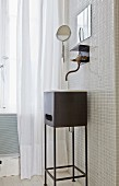Black metal washstand below vintage-style wall-mounted tap on white mosaic wall tiles