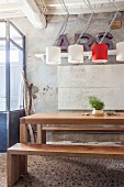 Simple, exotic-wood dining table and benches below designer lamps in rustic interior