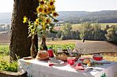Gedeckter Kaffeetisch mit Guglhupf, Sonnenblumen und sommerlichem Landschaftsblick