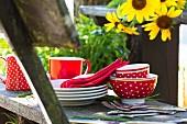 Rot-weisses Picknickgeschirr und Besteck auf rustikaler Holzbank neben Sonnenblumen