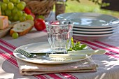 Place setting next to stacked white plates on striped tablecloth outdoors