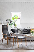 Sofa and armchair with footstool in shades of grey below sloping ceiling in Scandinavian living room