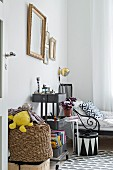 Gilt-framed pictures and storage trays on trolley in boy's bedroom