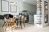 Dining area, fitted kitchen and vertical bookcase in doorway in open-plan interior
