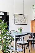 Hellgrauer Holztisch mit Frühlingsblumen und schwarzen Bugholzstühlen