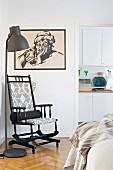 Schwarzer Holzschaukelstuhl neben Stehleuchte und schwarz gerahmter Zeichnung