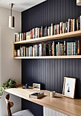 Black wood paneling with book boards over desk top