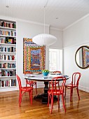 Dining area with a round table and red bentwood chairs in an old building with a bookcase and a colorful painting