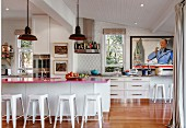 Pink kitchen countertop on kitchen counter with bar stool in open kitchen with retro flair