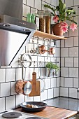 Utensils hung on tiled wall in corner of kitchen