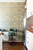 Dark green retro bar stools against floral wallpaper in kitchen