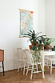 White wooden chairs around potted house plants on dining table in retro interior