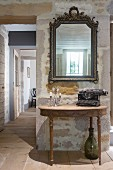 Typewriter and candelabra on antique console table below mirror on wall