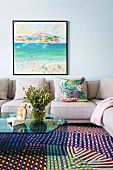 Gray corner sofa with glass coffee table on carpet with colorful geometric patterns