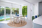 Light-flooded living room with a round dining table and a view of the pool in the garden through blinds