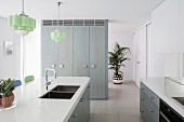 Simple kitchen in white-gray-blue with tiled floor, kitchen island and pastel green ceiling lights