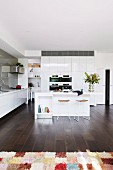 Modern, open kitchen with glossy white fronts
