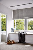 Upholstered bench in front of the window with a striped roller blind