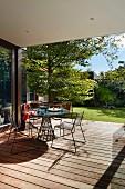 Delicate metal garden furniture on the terrace facing the garden
