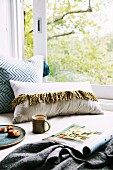 Cozy seat by the window with pillows, magazine and cup