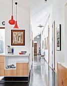 Heller Flur mit poliertem Betonboden und Kunstobjekten