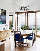 Oval table and chairs with blue velvet covers in the dining room