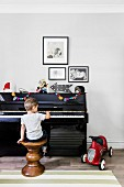 Boy is sitting on a turned wooden stool at the piano