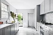 Große Küche im amerikanischen Stil in Grautönen mit Gartentür