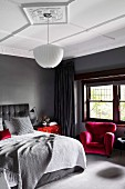 Elegant bedroom in shades of gray with red accents