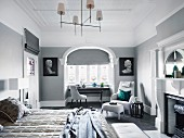 Elegant bedroom in gray tones with double bed, fireplace, upholstered armchair and table in front of the window